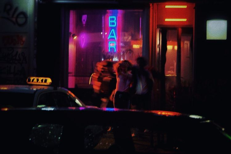 People in illuminated city seen through car windshield at night