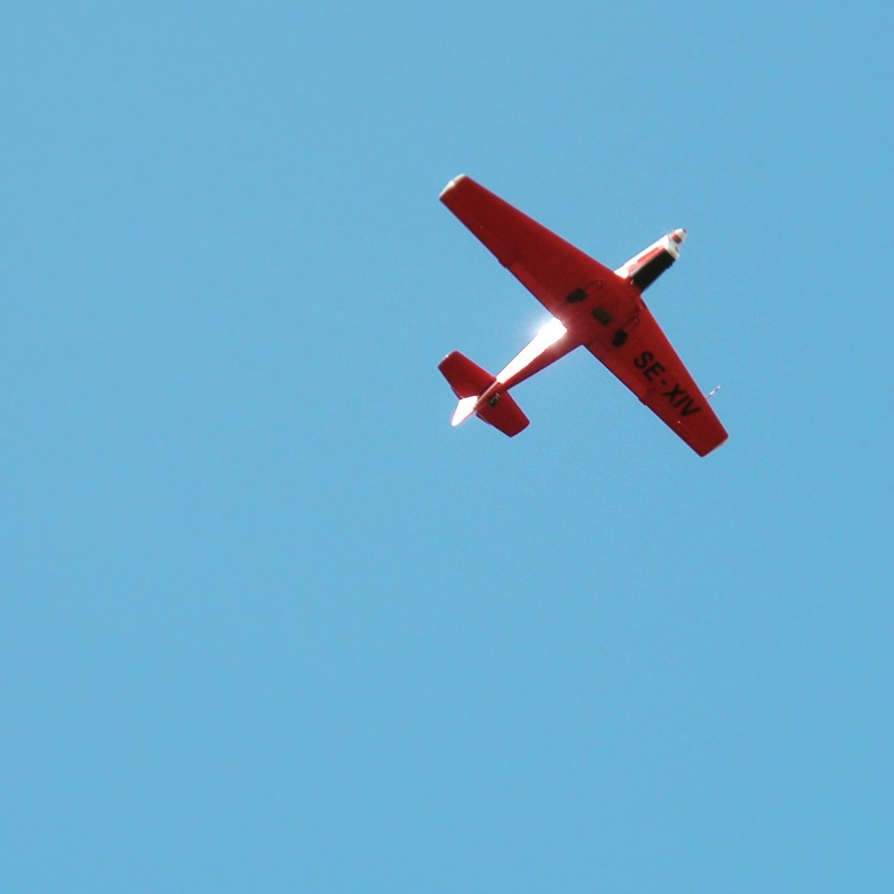 airplane, low angle view, flying, clear sky, copy space, air vehicle, blue, no people, day, transportation, red, journey, outdoors, model airplane, sky