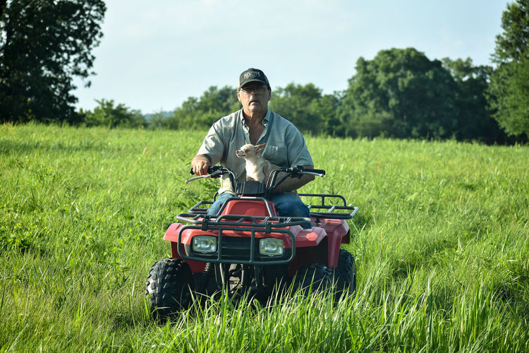 Man Holding Dog While Riding Quadbike In Field