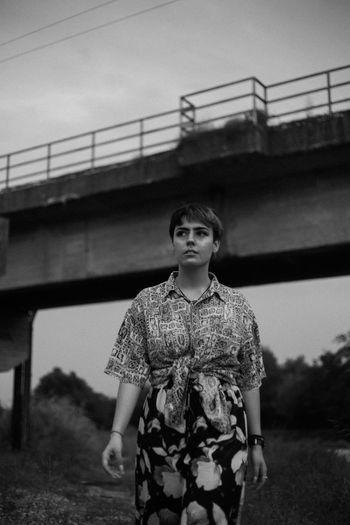 Portrait of woman standing against bridge