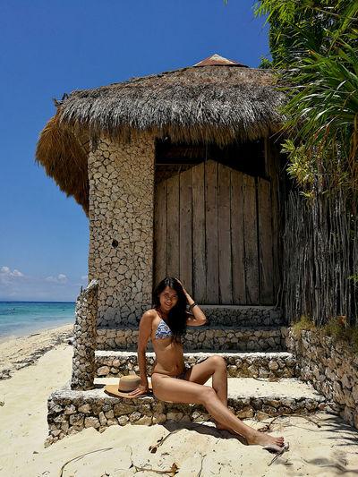 Portrait of woman in bikini sitting at beach