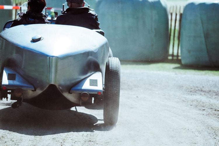 Rear View Of Men In Race Car On Road