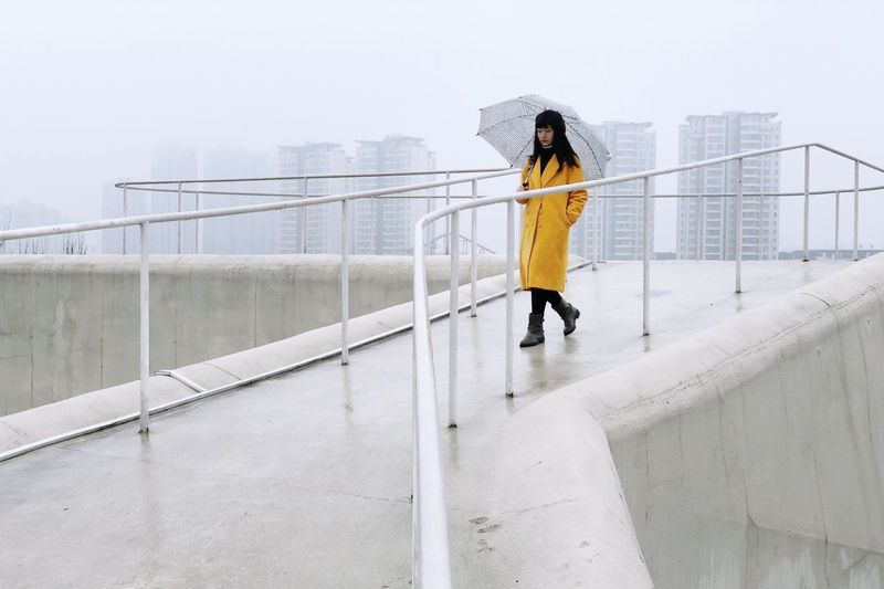 Rainy Days Umbrella Walking One Person Railing Lifestyles Architecture Real People Women Leisure Activity Outdoors