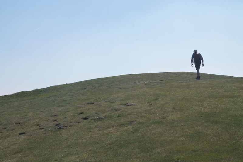 Man on landscape against clear sky