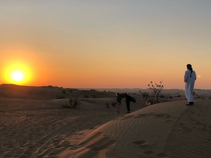 Rear View Of Man Standing On Sand Dune During Sunset
