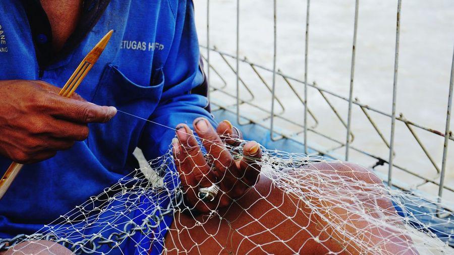 Close-up of man holding fishing net