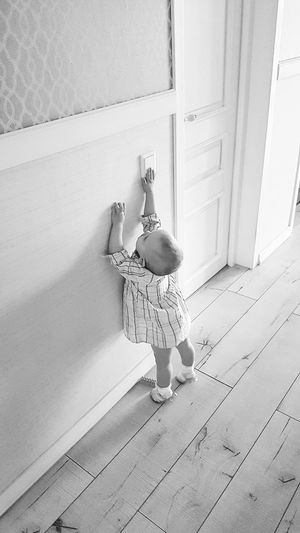 High angle view of toddler baby pressing light switch at home