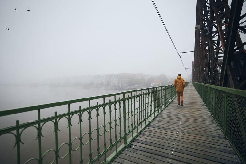 Man walking on footbridge against sky