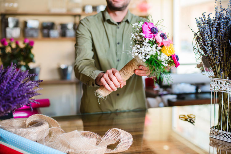 Midsection of man holding flower bouquet