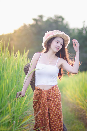 Young Women Young Adult One Person Field Three Quarter Length Land Leisure Activity Standing Real People Grass Beautiful Woman Plant Women Beauty Day Lifestyles Front View Focus On Foreground Smiling Nature Hairstyle Outdoors
