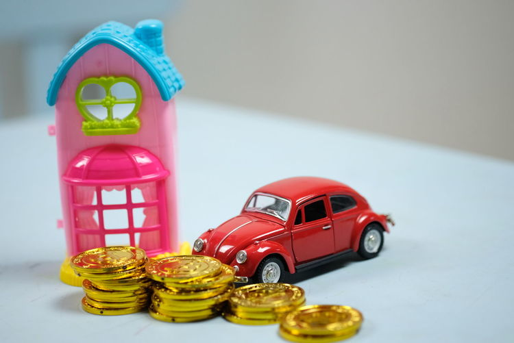 Close-up of toy car with coins and model home on table