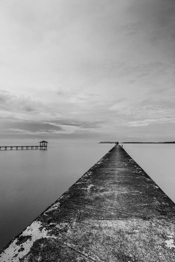 Black and white image of fishing jetties with one on an old walkway and one shack at far away. Dramatic Sky Lights EyeEm Selects Long Exposure Black Blackandwhite Jetty Fishing Outdoors Day Tranquility Sky No People Cloud - Sky Water Beauty In Nature Nature