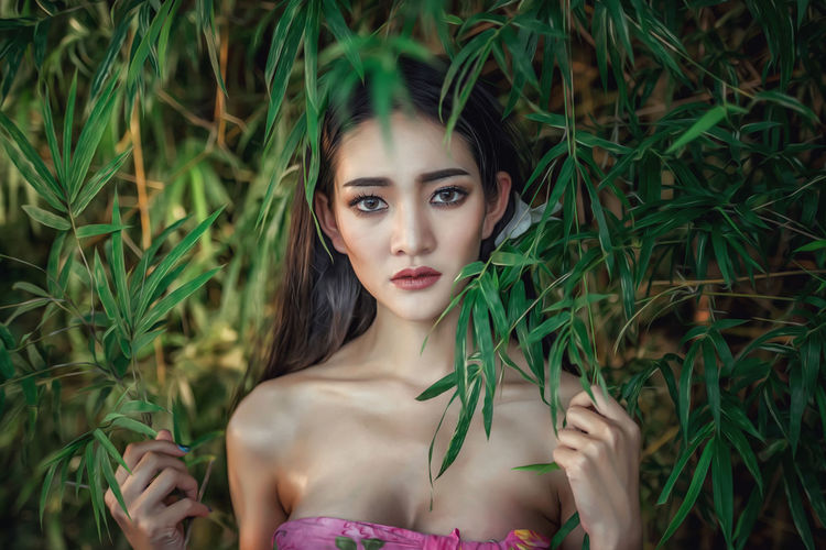 Portrait of beautiful young woman standing against tree