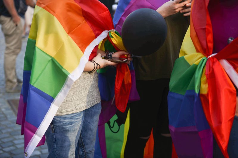 People Wearing Rainbow Flags During Parade In City
