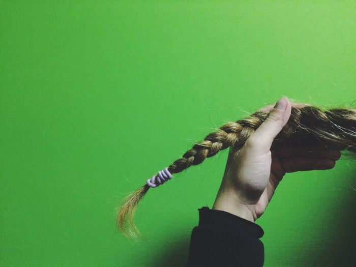 Cropped Hand Holding Braided Hair Against Green Background