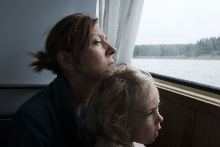 Close-up of mother with daughter looking away sitting by window