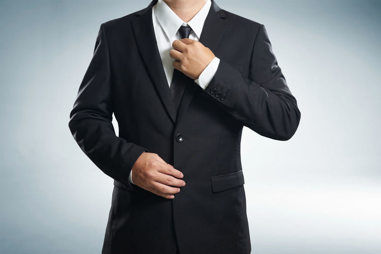 Midsection of businessman adjusting suit against gray background