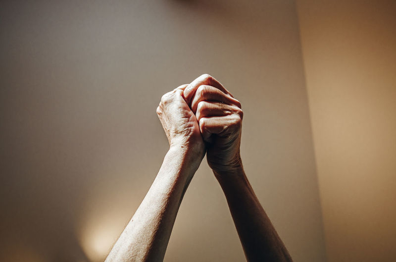 Cropped image of person holding hands against wall
