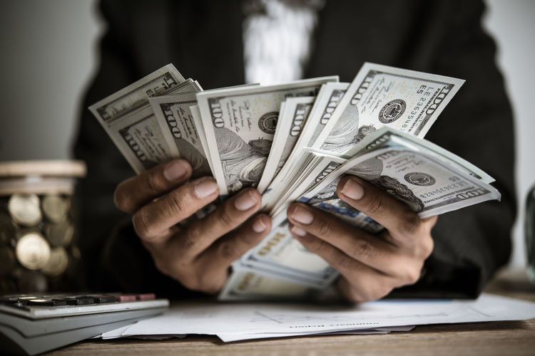 Midsection of businessman holding paper currency on table
