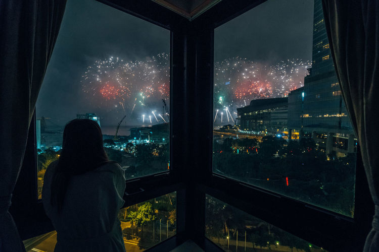Woman Looking At Firework Display During Night
