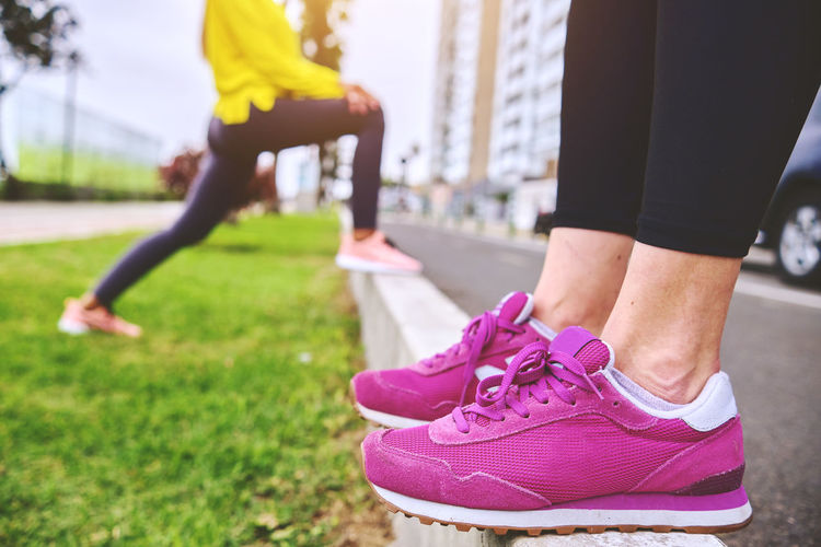 Low section of people in pink shoes