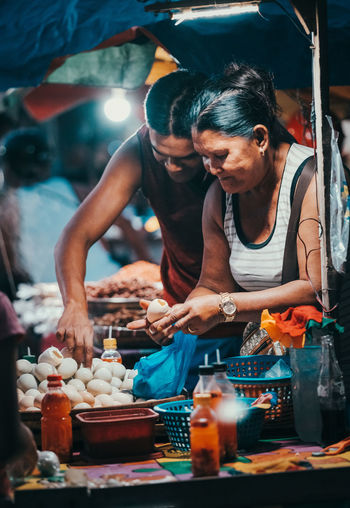 Woman with vegetables at market stall.