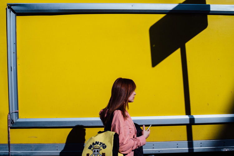 Side view of young woman against yellow wall