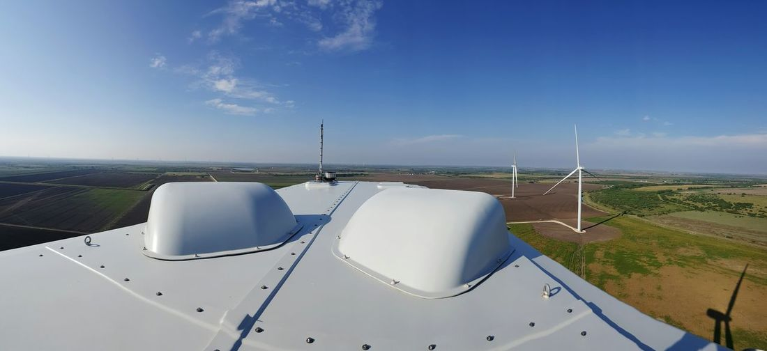 Cropped image of windmill turbine by agricultural landscape against sky