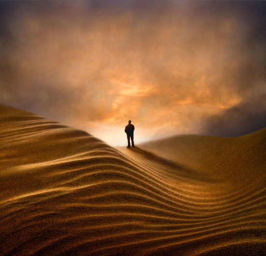 Silhouette man standing on sand dune against sky during sunset