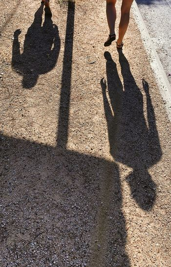 Shadow of man with umbrella standing on road