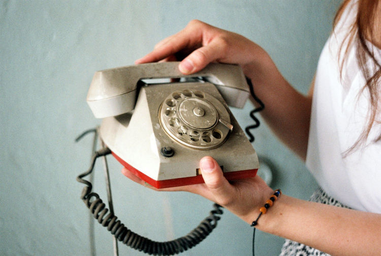 Midsection Of Woman Holding Rotary Phone Against Wall At Home