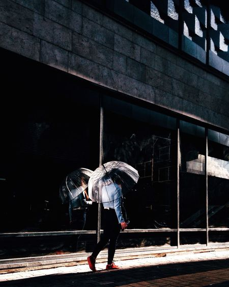 Woman with umbrella walking on the street Real People Lifestyles Built Structure Building Exterior Walking Women Full Length Light And Shadow Umbrella