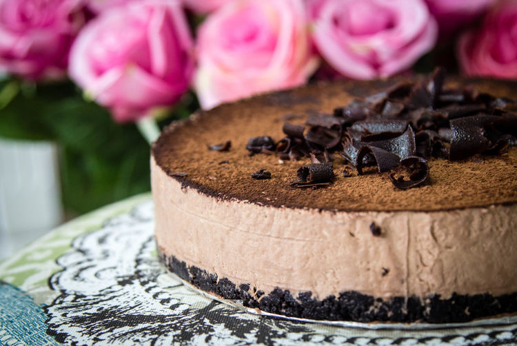 Close-up of chocolate cake by pink roses