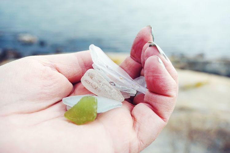 Close-up of hand holding semi-precious gemstones and glass