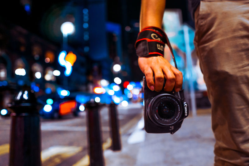Midsection of man photographing illuminated city at night