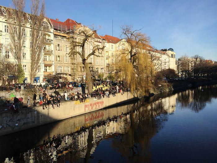 People by lake against buildings in city