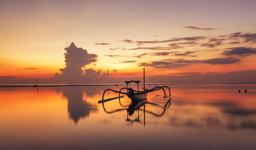 "Beautiful Sunrise Scene in Bali, Indonesia. The rowboat or ""Jukung"" is widely use as fishing boat by the local fisherman ASIA Bali, Indonesia Beauty In Nature Boat Calm Cloudy Dramatic Sky Idyllic Moody Sky Nature No People Orange Color Outdoors Reflection Sanur Beach Scenics Sky Sun Sunrise Sunset Tranquil Scene Travel Vacation Warm Colors Water"