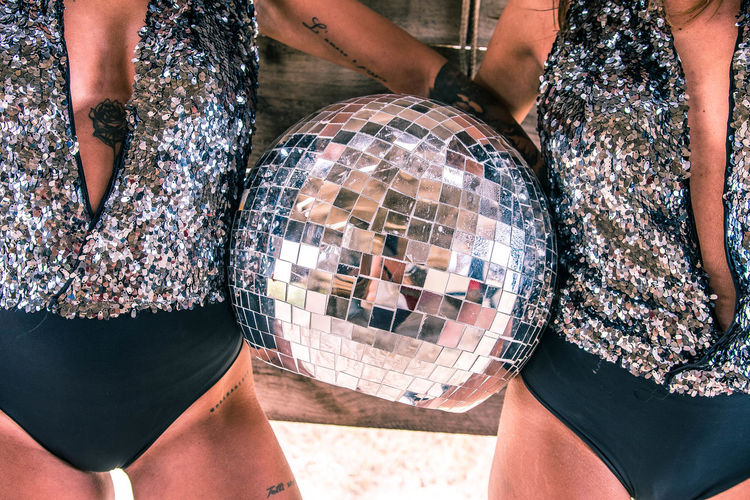 Midsection of female friends holding disco ball