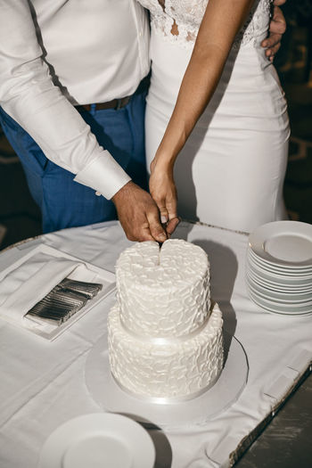 Midsection Of Couple Cutting Cake At Wedding Ceremony