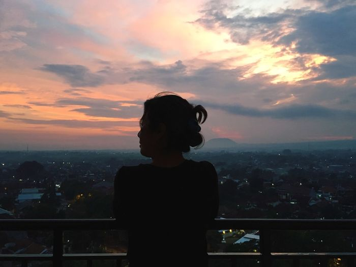 Rear view of woman standing by railing against cityscape during sunset