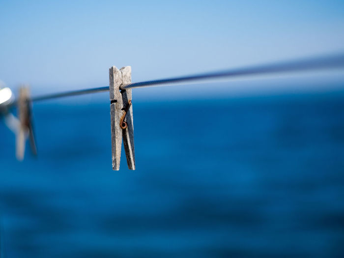 Close-up of clothespins hanging on rope against blue sky