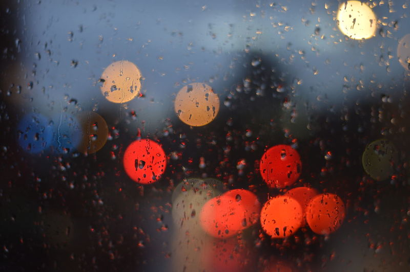 Close-up of wet glass window against defocused lights during rain