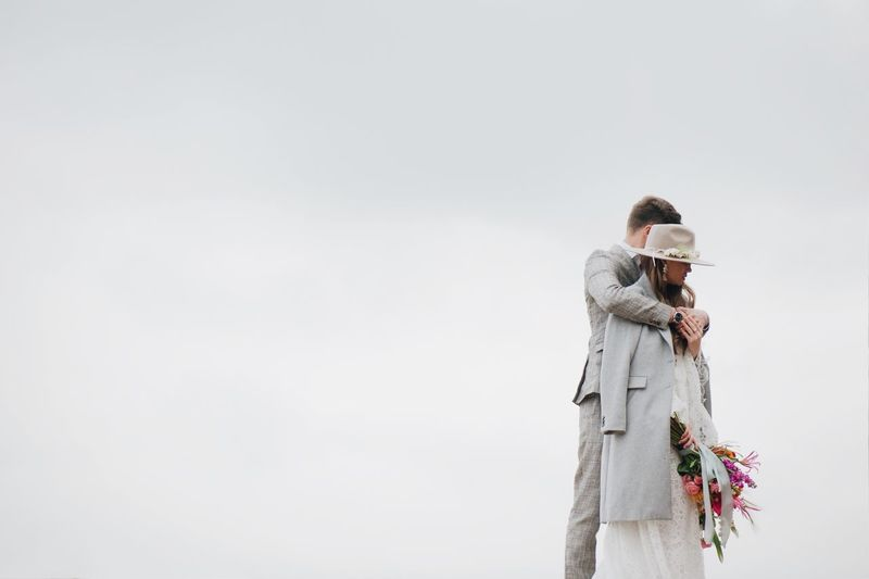Bride And Bridegroom Standing Against Clear Sky