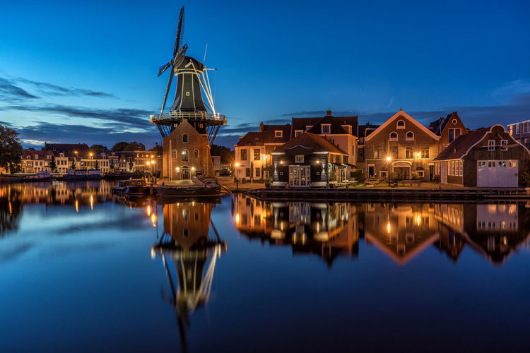 De Adriaan Windmill By River And Houses At Dusk