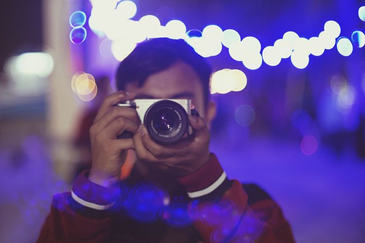 Young man photographing from camera at night