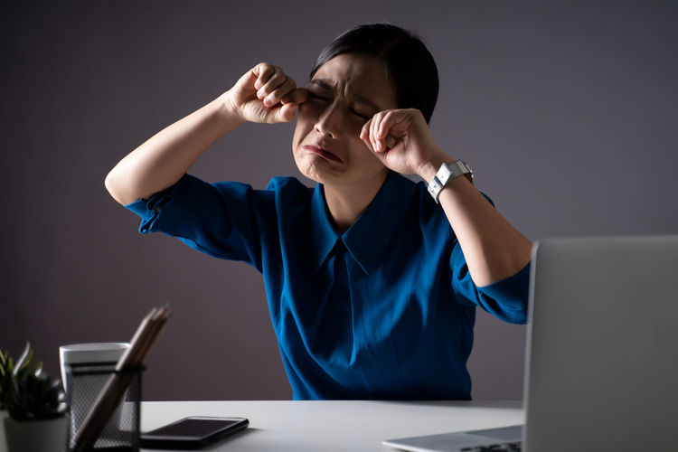 Close-up of young businesswoman crying at office