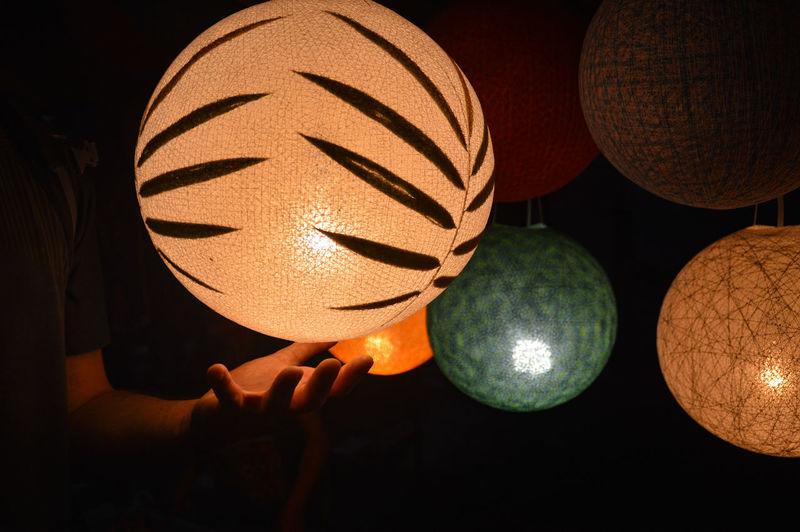 Close-up of hand under illuminated lantern in darkroom
