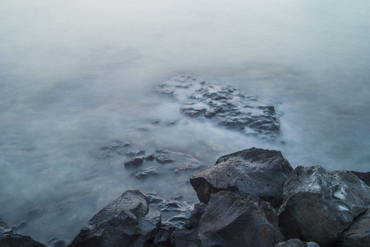 High angle view of rocky shore during foggy weather