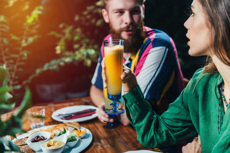 Young couple having drinks while dating in restaurant