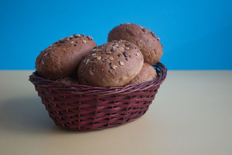 Food Food And Drink Freshness Basket Still Life Bread Indoors  No People Close-up Baked Blue Colored Background Studio Shot Bun Wicker Ready-to-eat Brown Bread Yellow Seeds Copy Space